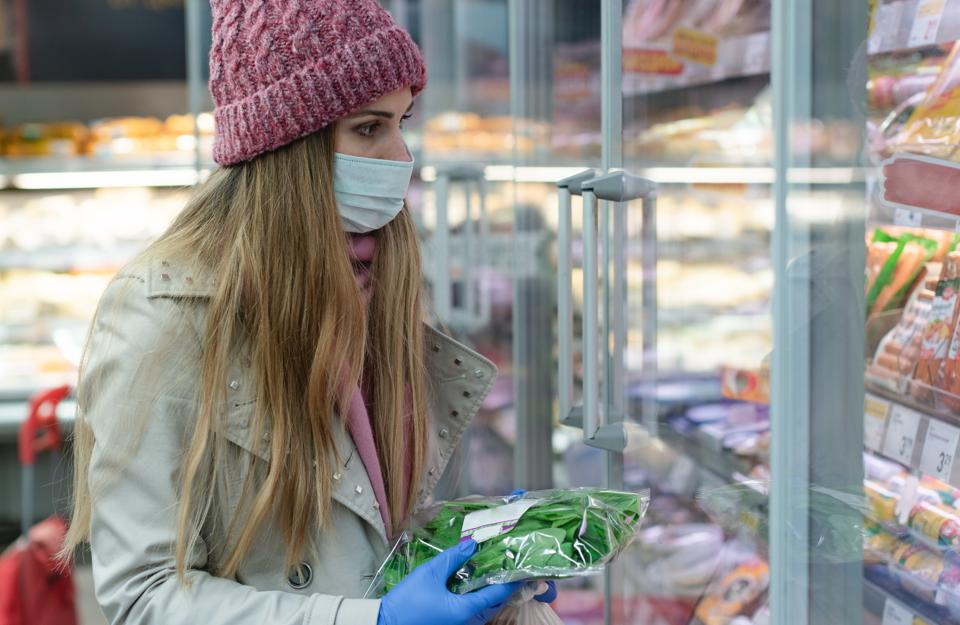 Woman in full corona outfit shopping in supermarket