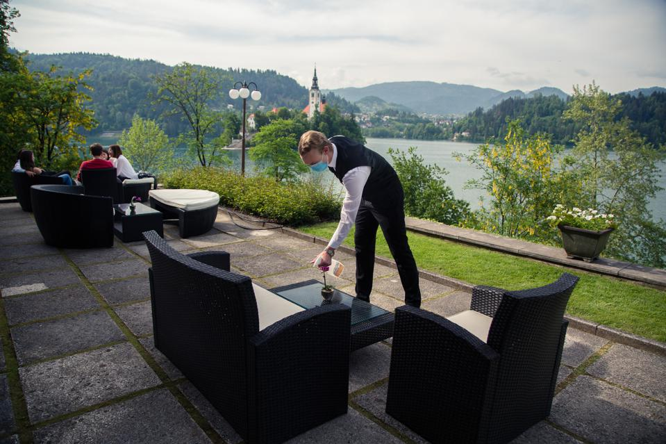 A waiter wearing a face mask at a hotel in Bled Slovenia disinfects tables