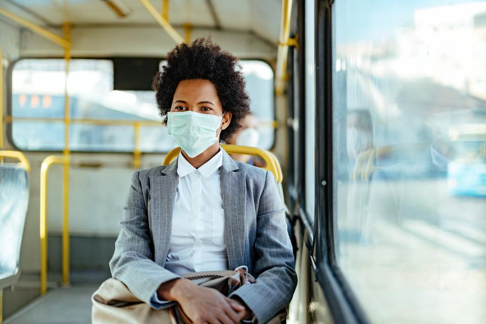 African American businesswoman with face mask for virus protection while commuting by bus.