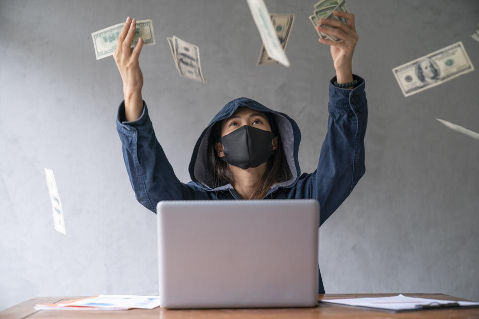 Hooded and medical mask-wearing hacker is seen behind laptop computer throwing dollar bills into the air
