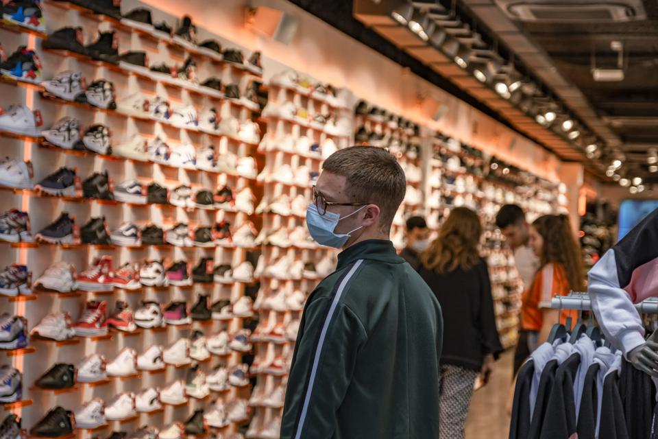 A man shopping at a shoe store while wearing a face mask as...