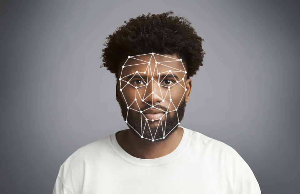 Facial recognition. African American man with polygonal mesh on his face against grey background