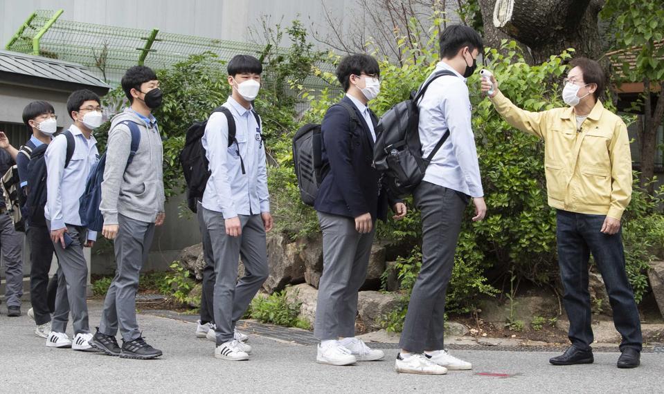 South Korea--High School seniors returning to school with temperature screening.