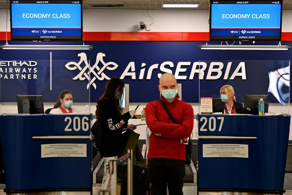 man in mask at Belgrade airport in Serbia As opens its borders to all travelers