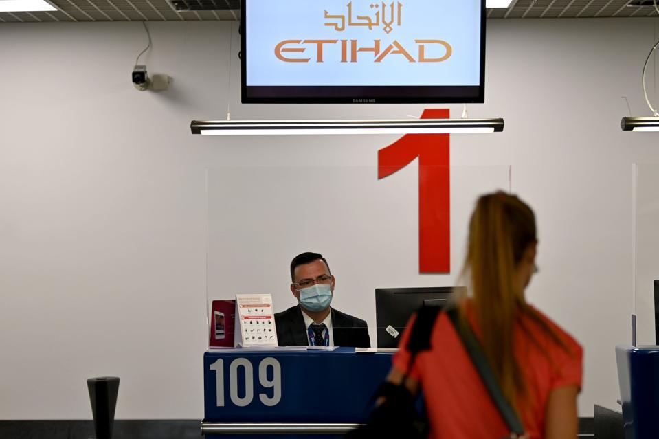 airport staff wearing face mask, behind plexiglass at Etihad Belgrade airport Serbia