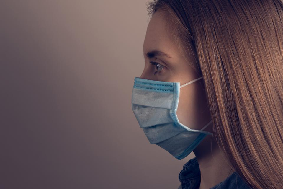 Closeup photo of woman wearing a facial PPE mask, looking aside against a grey background.