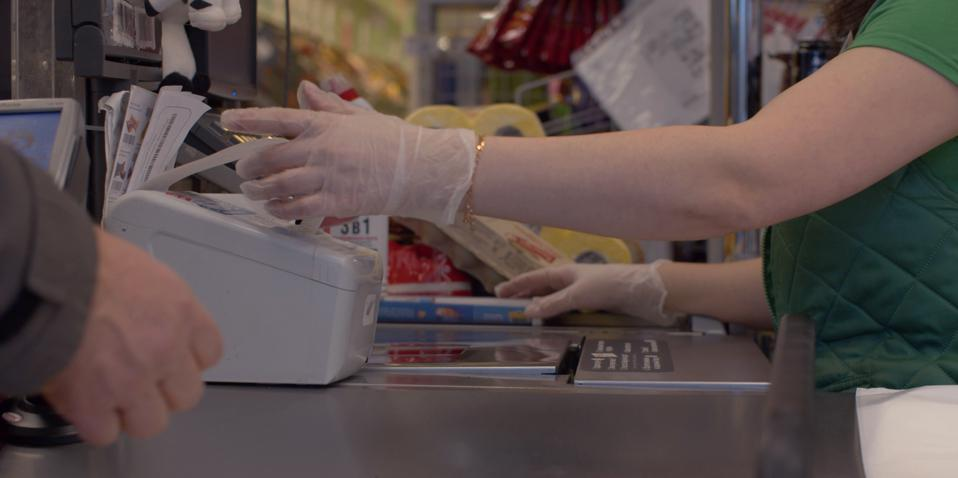 Hands of cashier taking check from cash register. COVID-19 pandemic