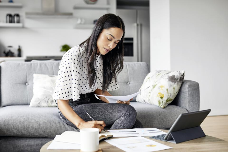 Woman analyzing documents while sitting at home