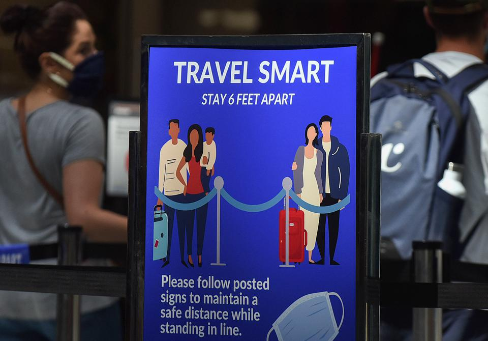 A sign reminding passengers to stay 6 feet apart is seen at...