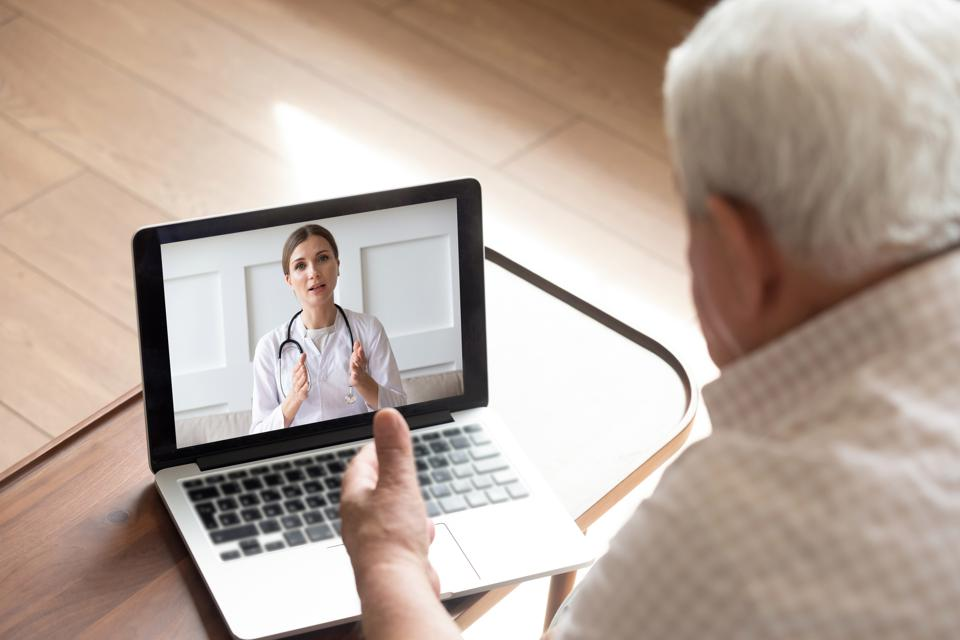 Close up older man talking with doctor online, video call