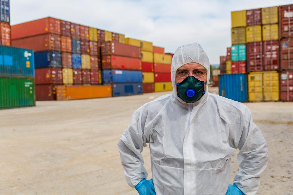 Worker in protective suit and Containers box from Cargo freight ship for import export