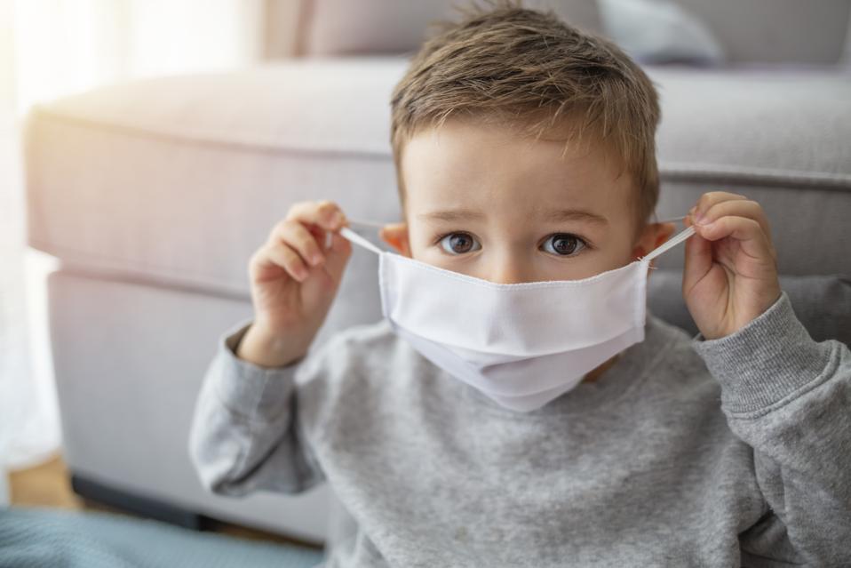 Little boy wearing anti virus mask staying at home.