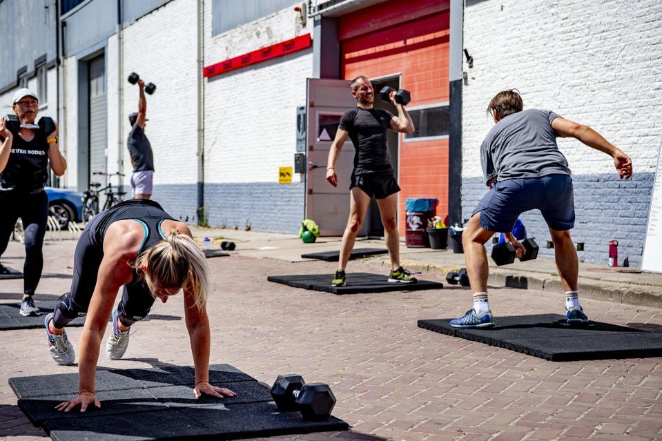 People exercise outside crossfit gym amid coronavirus crisis...