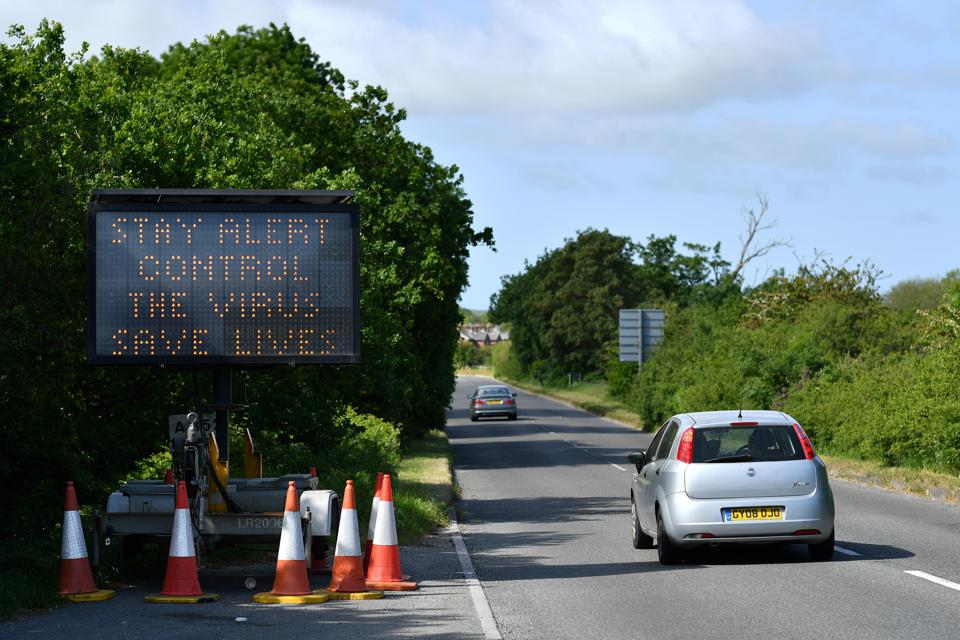 A driver passes a sign reading ″Stay Alert, Control the virus, Save Lives″ as cars travel towards the coast on the south coast of England on May 24, 2020.