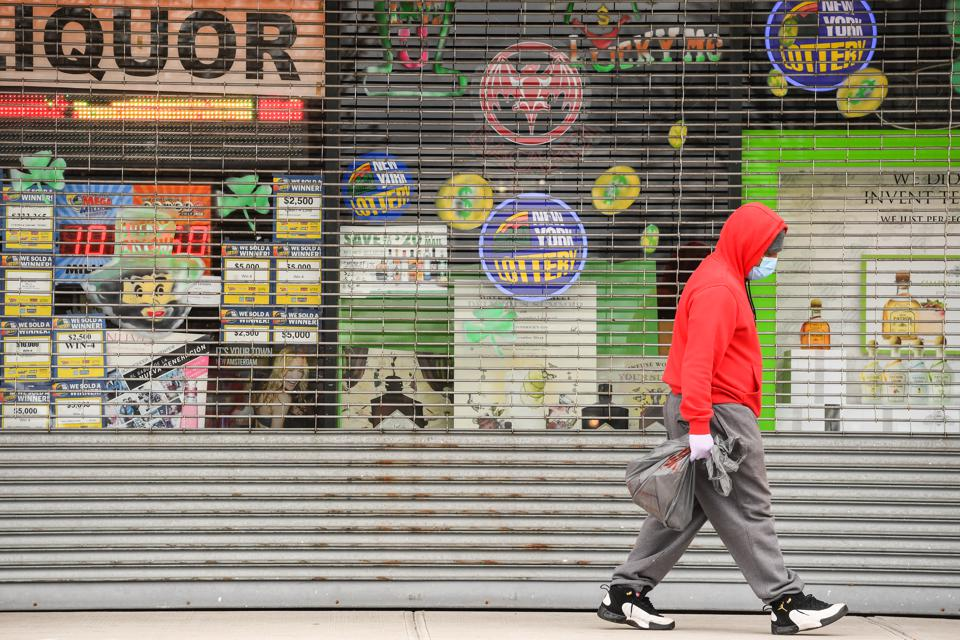 Pedestrian walks past closed stores during pandemic