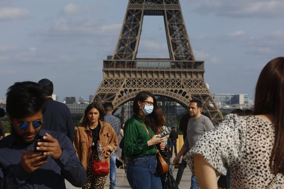Tourists at the Trocadero Place in front of the Eiffel Tower in Paris .