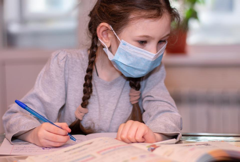 School girl in medical mask does homework.