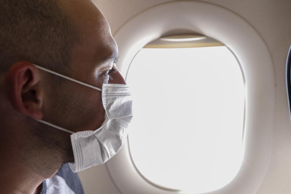 Cropped portrait of man in respirator mask flying on a plane.