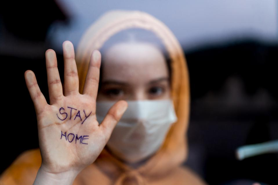Person wearing a surgical mask, looking through window, with 'stay home' written on hand.