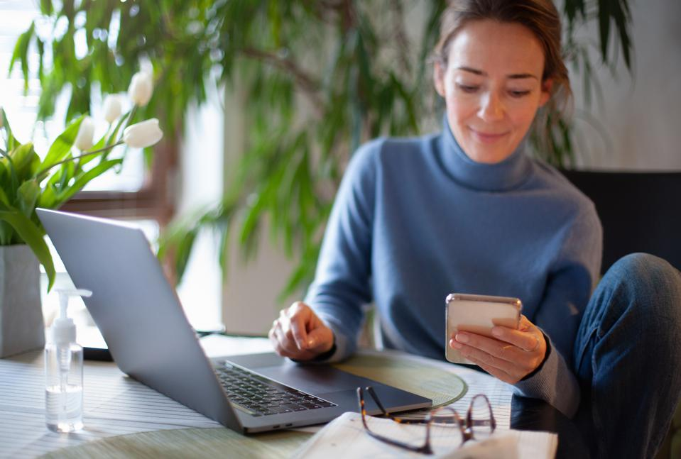 Woman working from home using laptop computer, reading text message on mobile phone