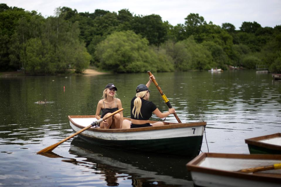 two woman in a rowing boat in Epping Forest, East London, United kingdom Europe