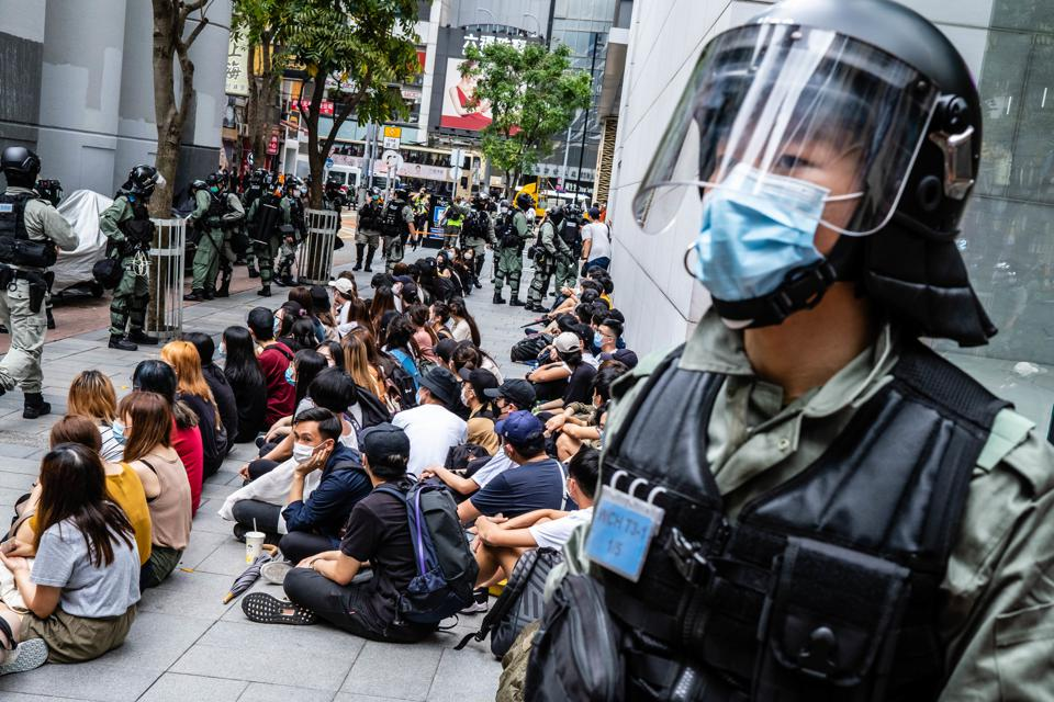 Riot police round up a group of protesters during the...