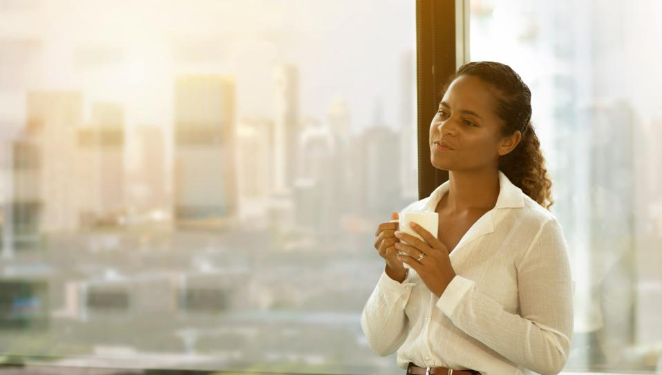 Attractive Young african american  business woman drinking  coffee while standing at  window in  office on cityscape background in morning light . happy black female enjoy tea relaxing on big city