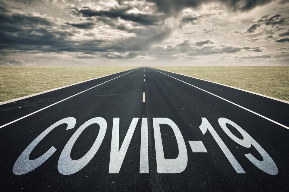 Covid-19 written on a road, dark clouds, coronavirus epidemic crisis concept