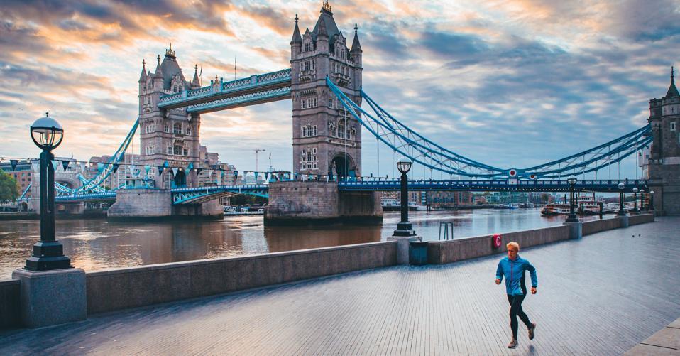 Lone runner, London streets in Coronavirus time. Tower Bridge in background.