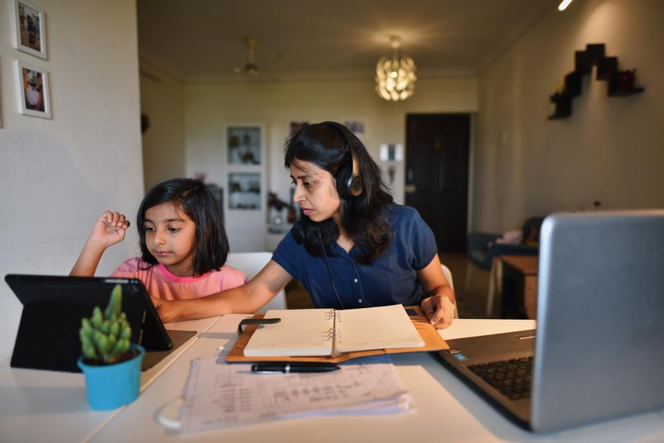 Woman working from home while daughter using digital tablet