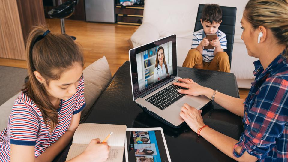 Mother talking with doctor on laptop while watching her two kids