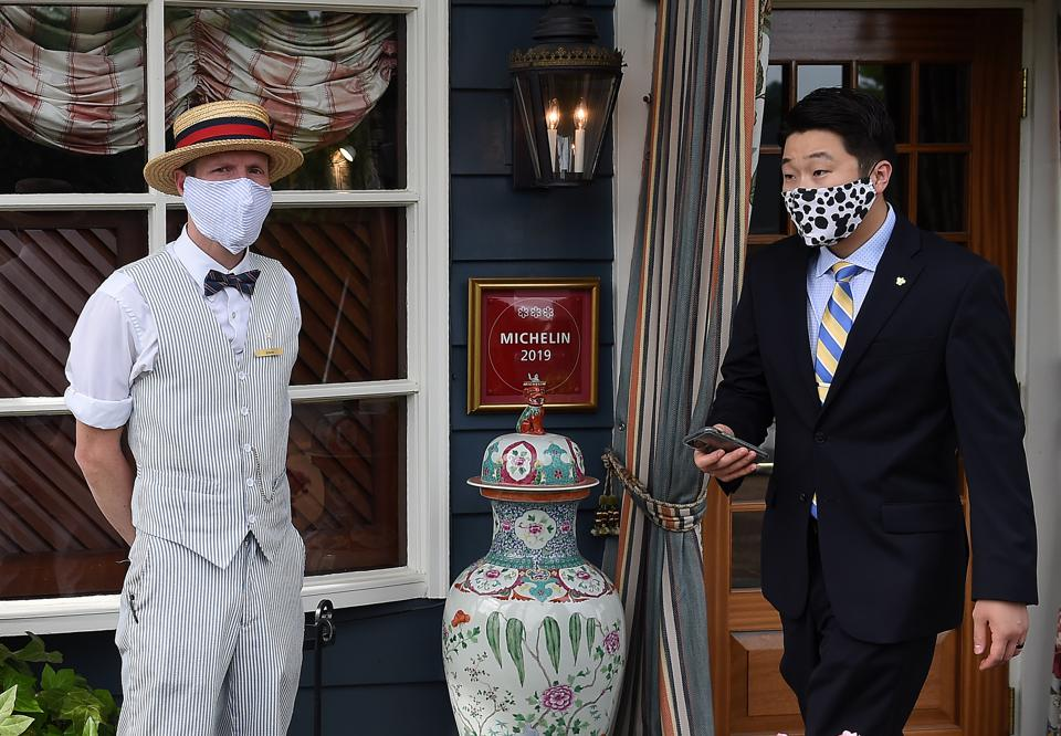 Employees outside The Inn at Little Washington, a double Five Star (Forbes Travel Guide), Triple Michelin Star hotel and restaurant on the first day of Virginia's phase one reopening, May 29, 2020.