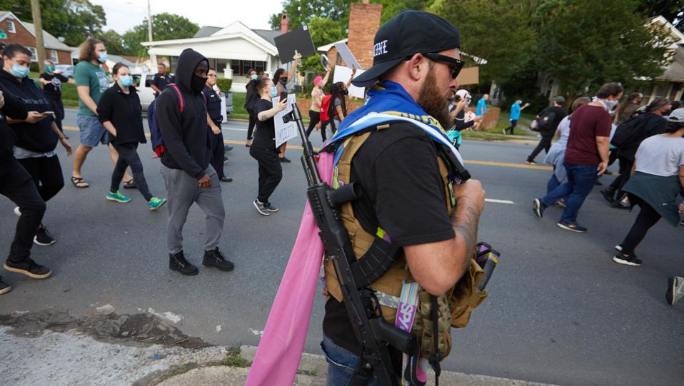 A member of the far-right militia, Boogaloo Boys, walks next to protestors US-POLITICS-POLICE-JUSTICE-RACISM