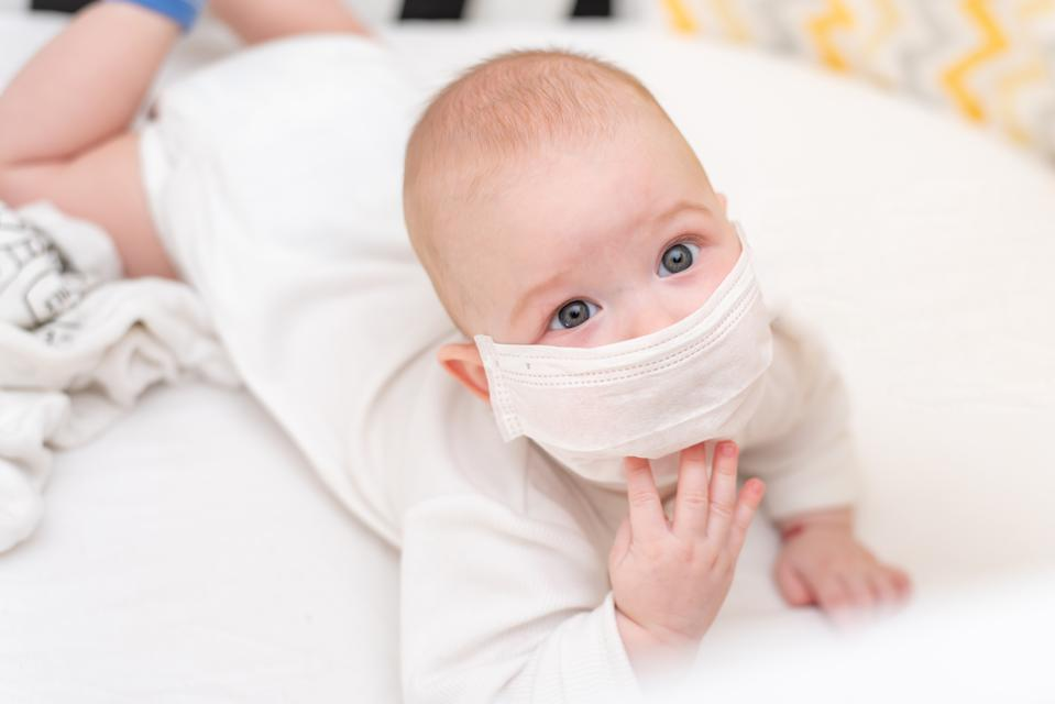 Baby in a medical mask lies in quarantine at home during the coronavirus and covid-19 pandemic.
