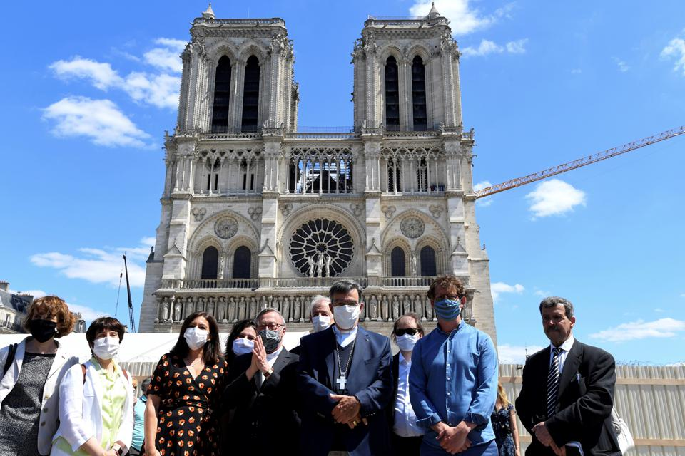 Paris mayor Anne Hidalgo (3rd L) and Paris Archbishop Michel Aupetit (C), pose in front of Notre-Dame de Paris Cathedral on the first day of the reopening of the Parvis Notre-Dame also knows as Place Jean-Paul-II.