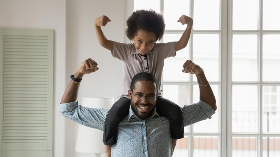 son sitting on father's shoulders