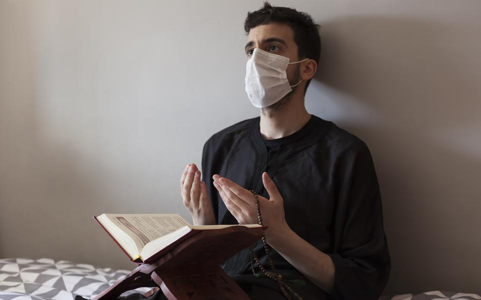 Muslim wearing a mask, praying and holding the Holy Quran.