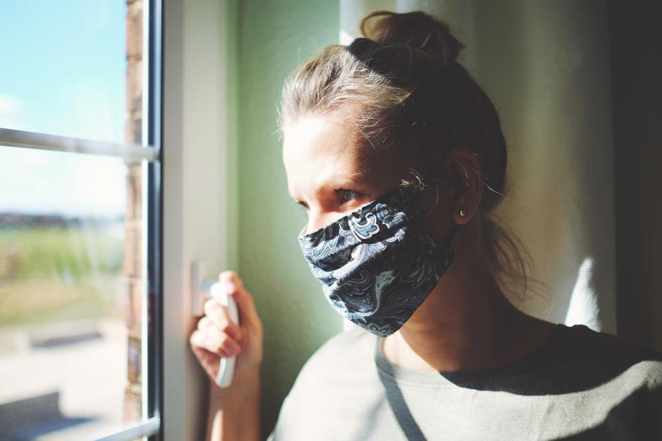 Pretty woman in quarantine with mask, looks out the window
