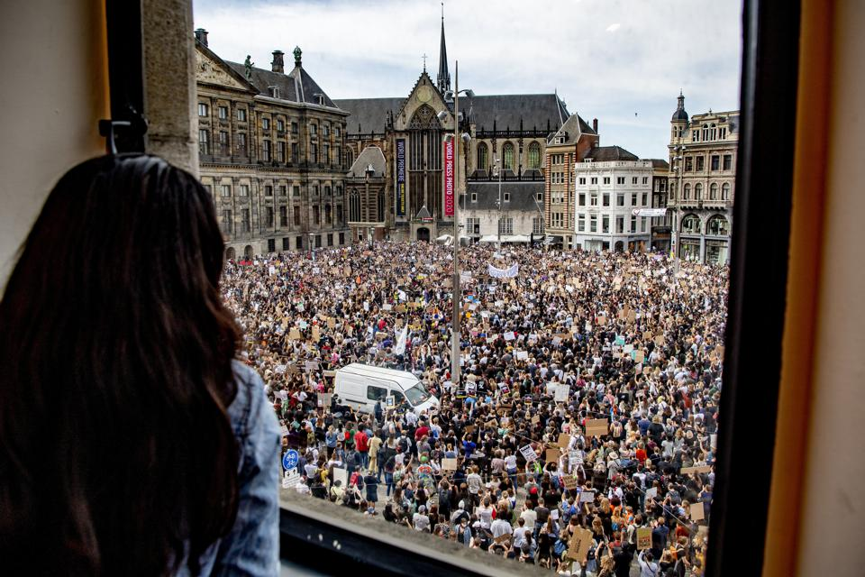 A woman looks at a crowd gathering at the Dam square during...