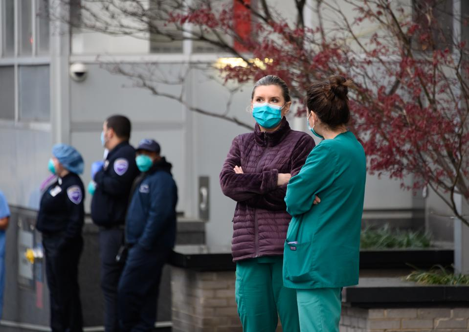 Hospital and emergency services workers in masks outside NYU Langone Health hospital in New York City.