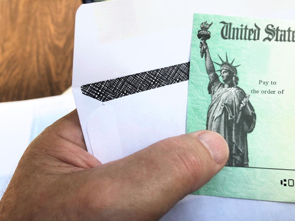 Senior's hand holding a Federal treasury check