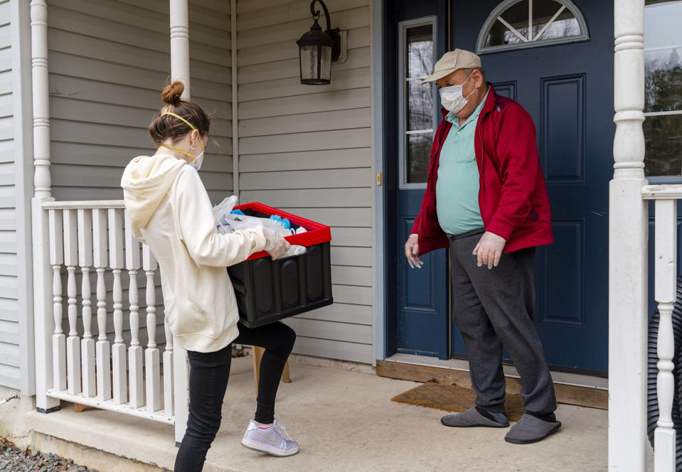 Young woman wearing protective n95 mask, a courier, is delivering the groceries packed into the reusable plastic bins to a customer, a senior man, during COVID-19 outbreak.