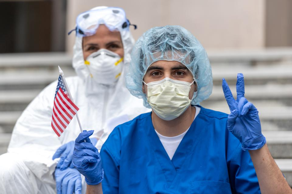 Health care worker during a break looking at the camera holding a US flag showing a two fingers victory sign