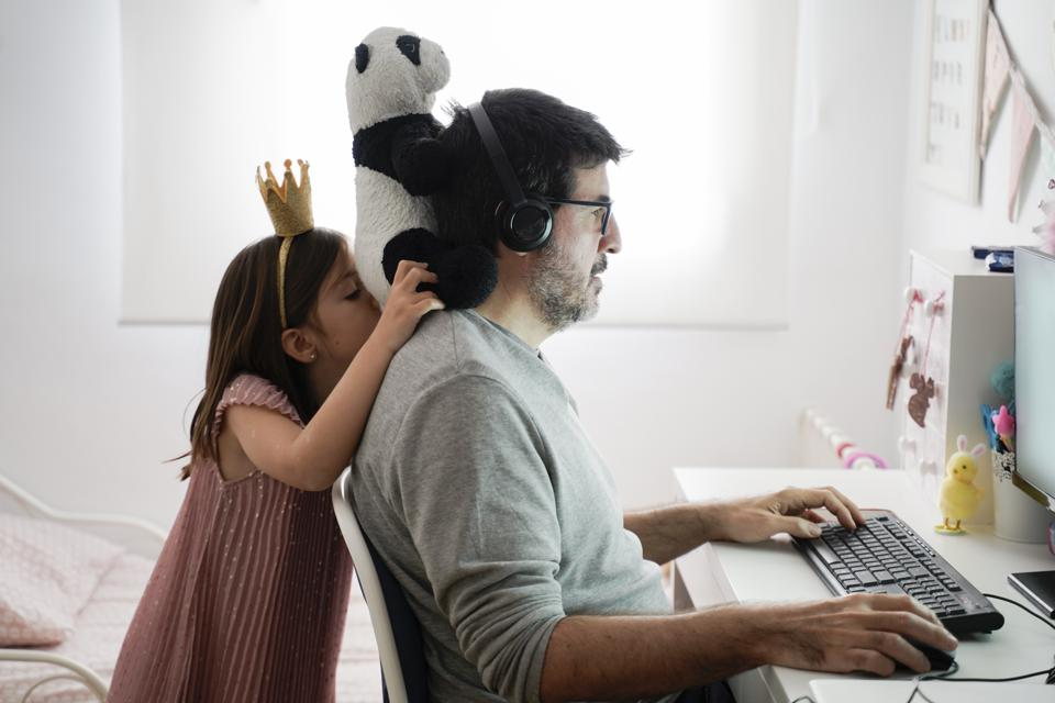Man doing telework and a little girl playing around
