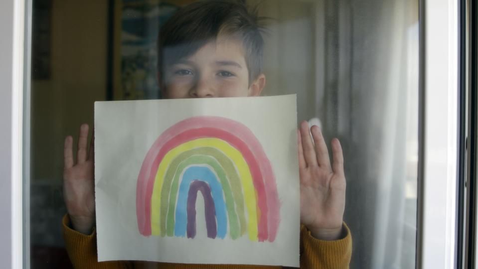 Boy sticking his rainbow drawing on home window. Coronavirus Quarantine Concept