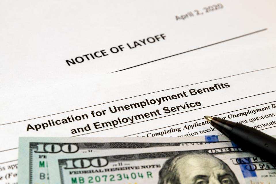 Job layoff notice and application for unemployment insurance benefits paperwork. Concept of Covid-19 coronavirus and stay at home order impact on economy