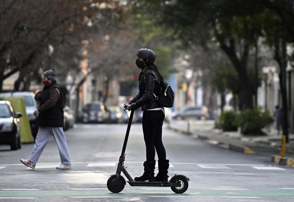 Woman wearing helmet rides a scooter.