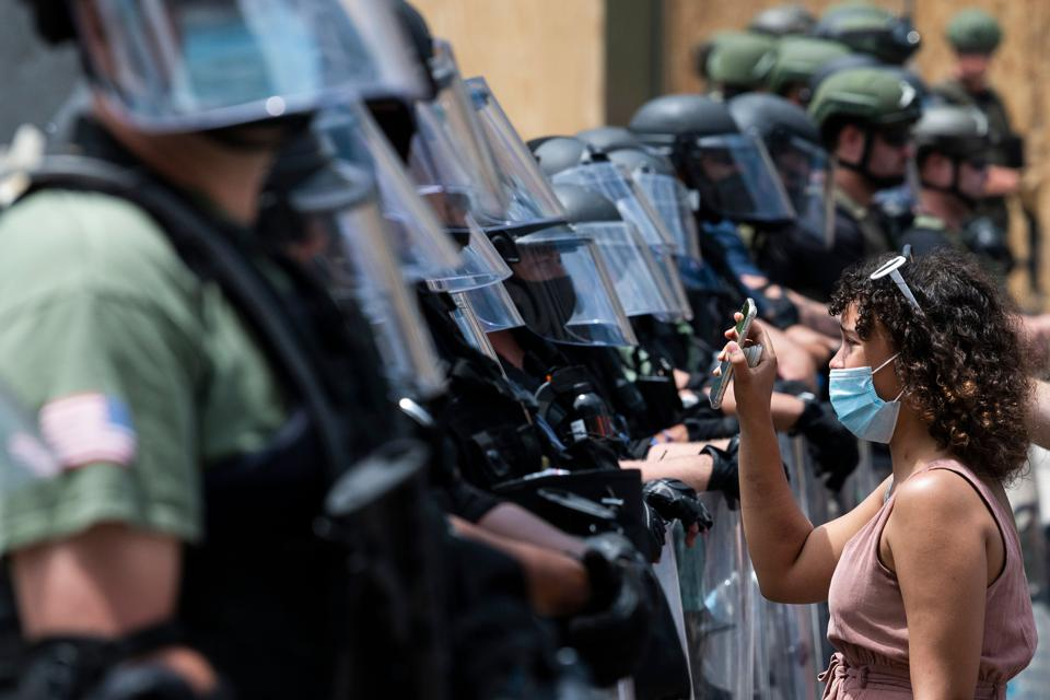 A protester shows security agents a picture of George Floyd on her phone. (Photo by JIM WATSON/AFP via Getty Images)