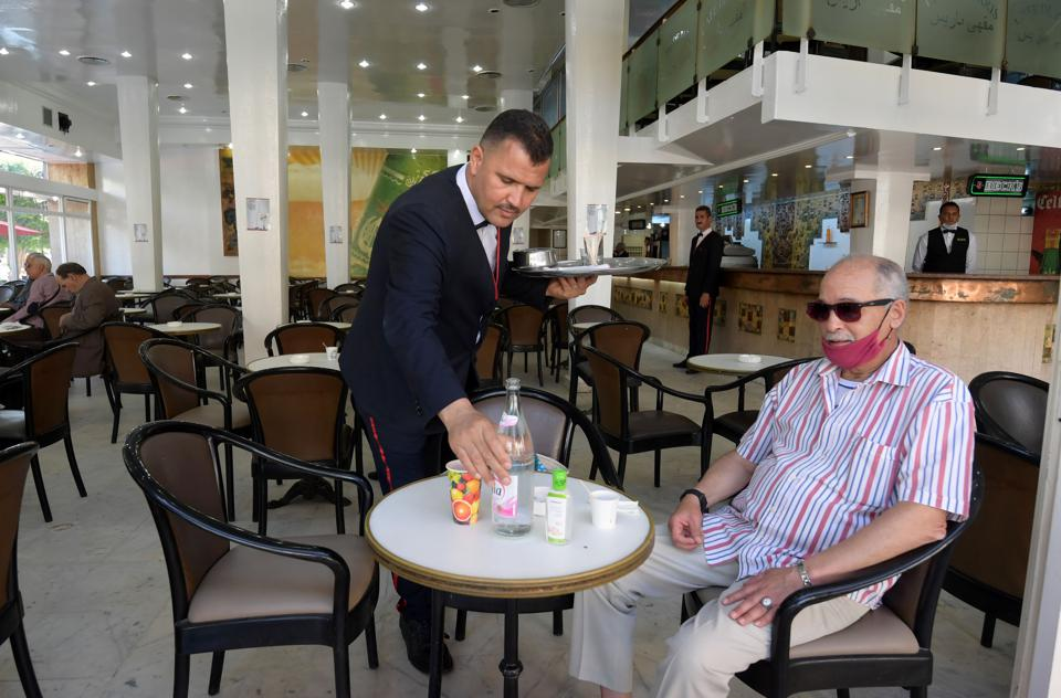 A waiter serves a man a drink in an almost empty cafe in Tunisia. The customer is wearing a mask but has dropped it below his mouth and nose.
