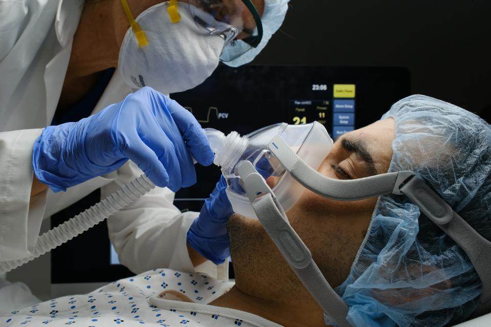 Doctor checks on Covid-19 infected patient while connected to a ventilator